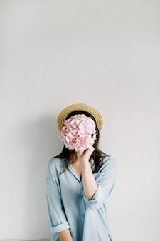 Jovem mulher segura buquê de flores de hortênsia rosa na superfície branca.