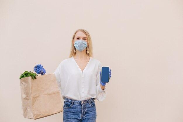 Jovem mulher segura o smartphone de compra de supermercado de saco de papel.