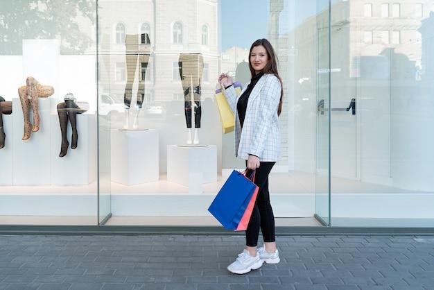 Jovem mulher segura pacotes multicoloridos na superfície das vitrines. compras no shopping.