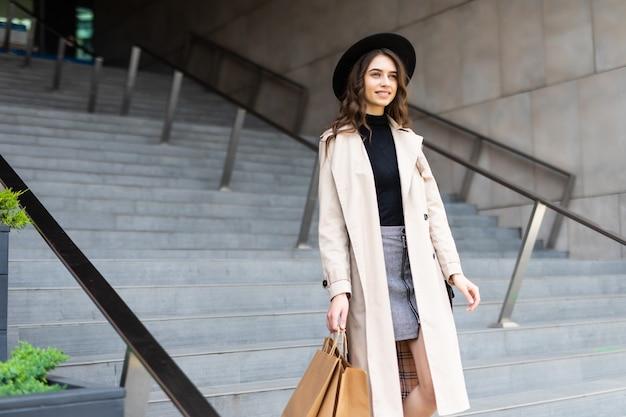 Jovem mulher segura sacolas de compras caminha em direção às portas de um shopping center exclusivo.