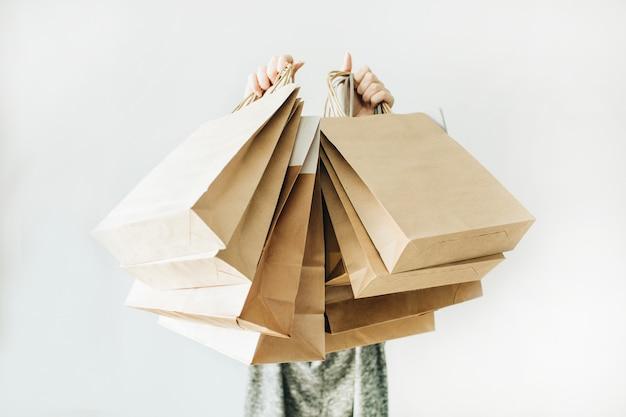 Jovem mulher segura sacos de papel artesanal na superfície branca.