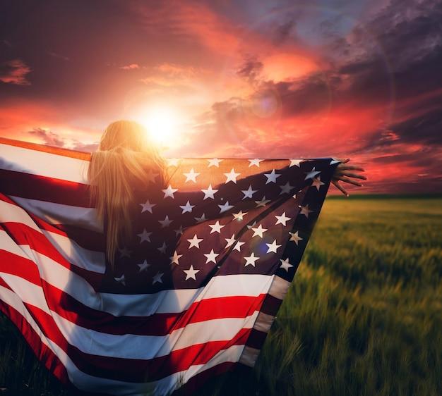 Jovem mulher segurando a bandeira americana ao pôr do sol. américa festeja o dia 4 de julho.