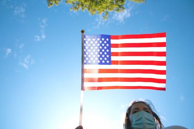 Jovem mulher segurando a bandeira americana no céu azul com luz solar e máscara de segurança para covid-19 acenando para eua