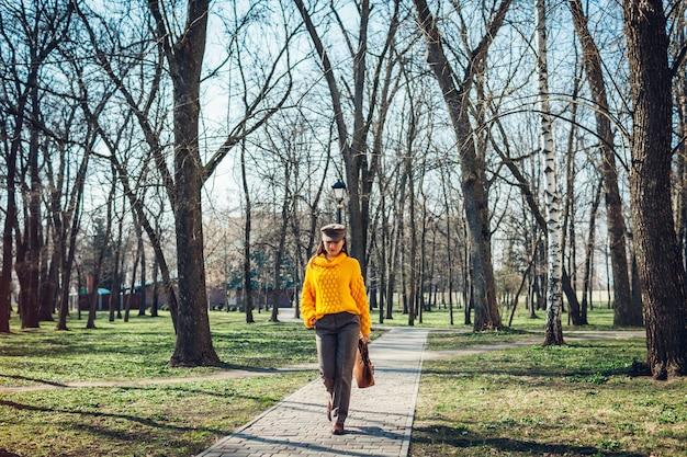 Jovem mulher segurando a bolsa elegante e vestindo blusa amarela.