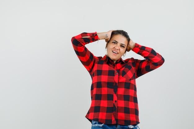 Jovem mulher segurando a cabeça com as mãos em camisa quadrada, shorts e olhando bonito, vista frontal.