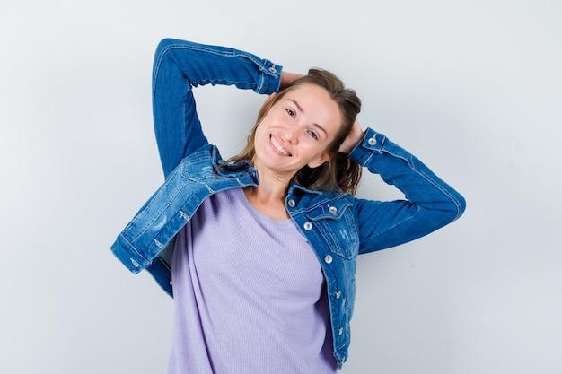 Jovem mulher segurando a cabeça com as mãos na camiseta, jaqueta e parecendo feliz. vista frontal.