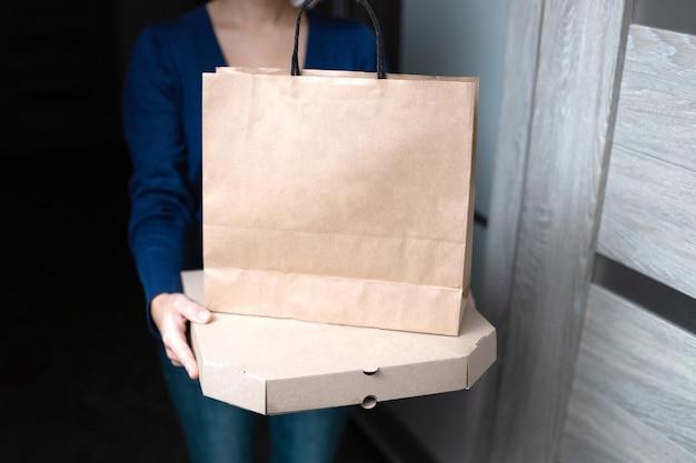 Jovem mulher segurando a caixa de pizza de papelão em branco e a sacola de papel.