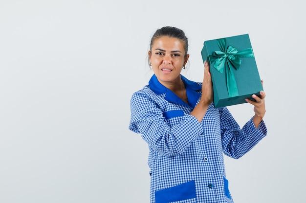 Jovem mulher segurando a caixa de presente com camisa de pijama azul guingão e linda vista frontal.