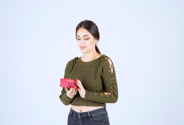 Jovem mulher segurando a caixa de presente em fundo branco.