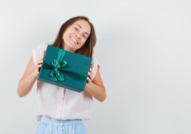 Jovem mulher segurando a caixa de presente em t-shirt, saia e olhando alegre, vista frontal.