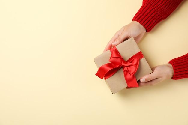 Jovem mulher segurando a caixa de presente na cor de fundo, espaço para texto