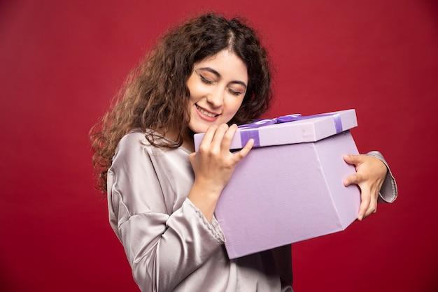 Jovem mulher segurando a caixa de presente roxa.