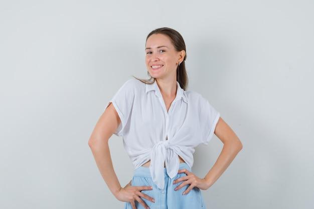 Jovem mulher segurando a cintura com as mãos na blusa e saia e com uma aparência charmosa