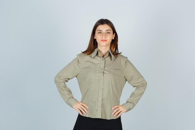 Jovem mulher segurando a cintura com as mãos na camisa, saia e parecendo confiante