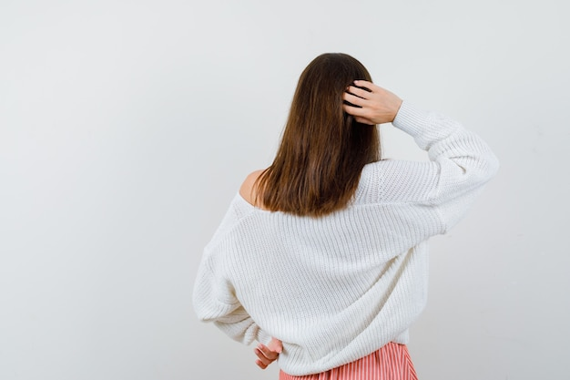 Jovem mulher segurando a mão atrás da cabeça em um casaco de lã e saia, parecendo pensativa isolada