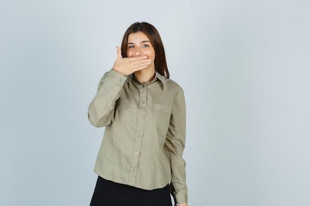 Jovem mulher segurando a mão na boca com uma camisa e parecendo feliz
