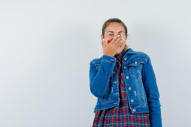 Jovem mulher segurando a mão na boca enquanto ri de camisa, jaqueta, vista frontal.