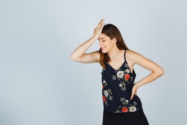 Jovem mulher segurando a mão na testa, blusa, saia e olhando alegre, vista frontal.