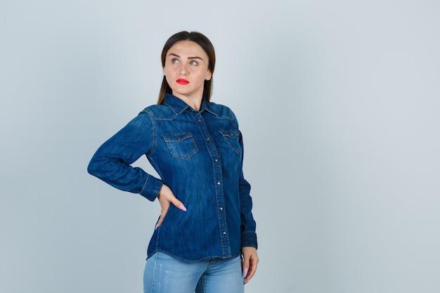 Jovem mulher segurando a mão no quadril enquanto olha para longe em uma camisa jeans e jeans e parece pensativa