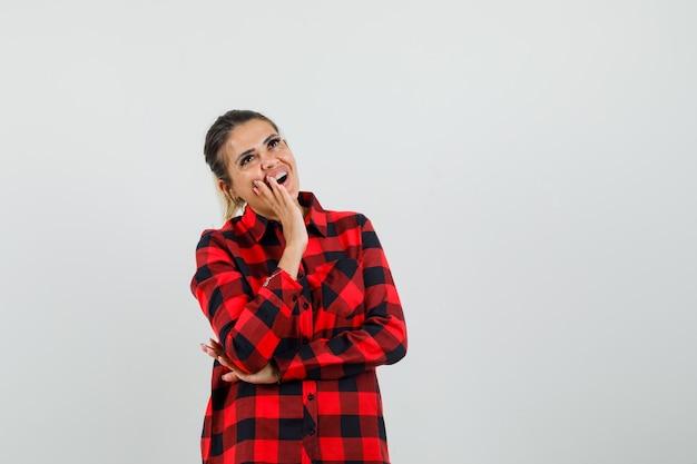 Jovem mulher segurando a mão perto da boca em uma camisa e parece feliz. vista frontal.