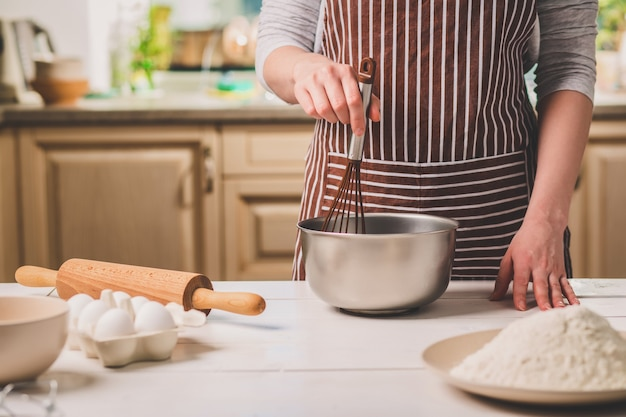 Jovem mulher segurando a tigela com massa e batedor, closeup. uma mulher com um avental listrado cozinhando na cozinha