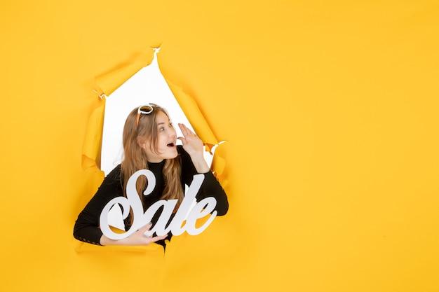 Jovem mulher segurando a venda escrevendo de frente, através de um buraco de papel rasgado na parede
