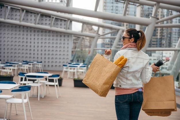 Jovem mulher segurando a xícara de café, andando com um saco de papel com baguete de pão branco comprido a sorrir