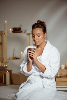 Jovem mulher segurando a xícara de chá relaxante no salão spa.