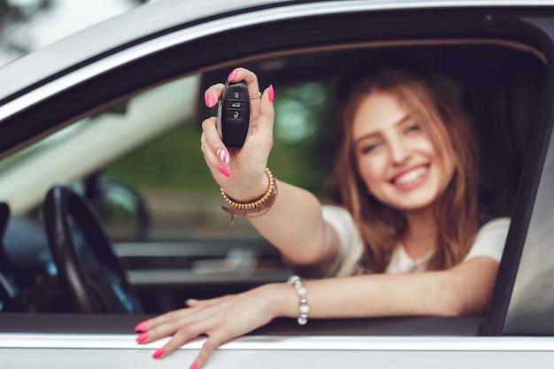 Jovem mulher segurando as chaves do carro novo