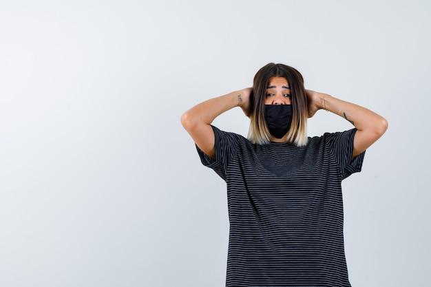 Jovem mulher segurando as mãos atrás da cabeça em um vestido preto, máscara preta e parecendo atormentado, vista frontal