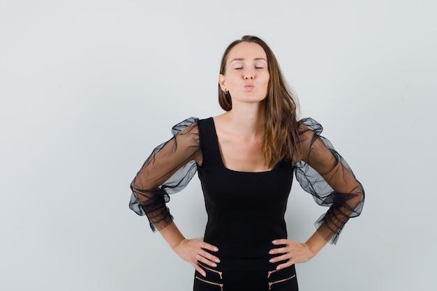 Jovem mulher segurando as mãos na cintura e mandando beijos para a câmera na blusa preta e calça preta e olhando encantadora, vista frontal.