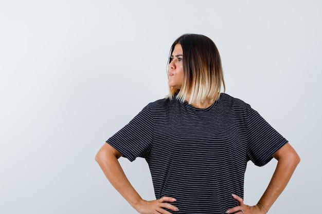Jovem mulher segurando as mãos na cintura, olhando para longe em um vestido preto e parecendo confiante. vista frontal.