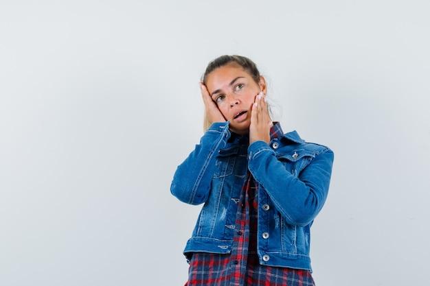 Jovem mulher segurando as mãos nas bochechas em camisa, jaqueta e parecendo tentador. vista frontal.