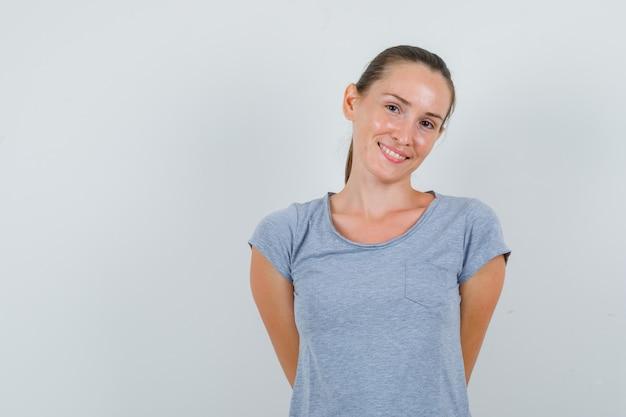 Jovem mulher segurando as mãos nas costas em uma camiseta cinza e parecendo alegre. vista frontal.