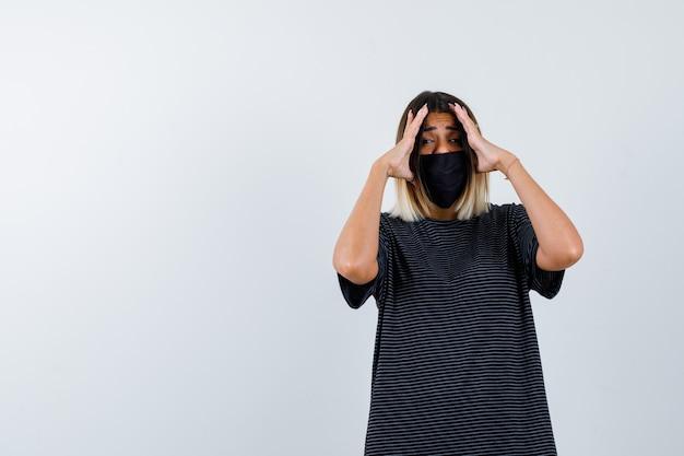 Jovem mulher segurando as mãos nas têmporas para ver claramente no vestido preto, máscara preta e olhando com foco, vista frontal.