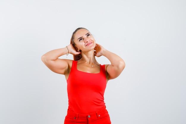 Jovem mulher segurando as mãos no pescoço, olhando para cima em uma blusa vermelha, calça e parecendo um sonho, vista frontal.