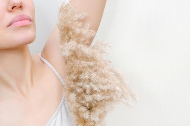 Jovem mulher segurando as mãos para cima e mostrando as axilas. a garota mostra uma axila limpa. retrato da beleza. remoção e depilação do cabelo.