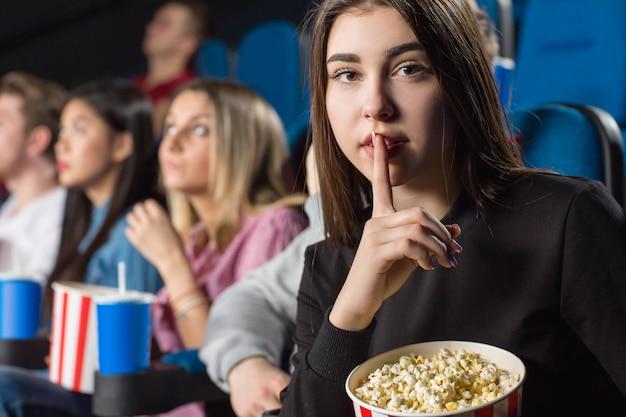 Jovem mulher segurando balde de pipoca, fazendo gesto calado para a câmera no cinema