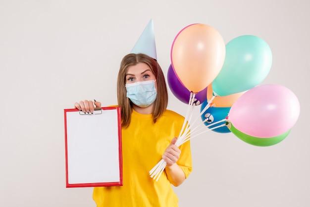 Jovem mulher segurando balões coloridos e nota na máscara em branco