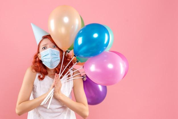 Jovem mulher segurando balões coloridos em máscara estéril em rosa claro