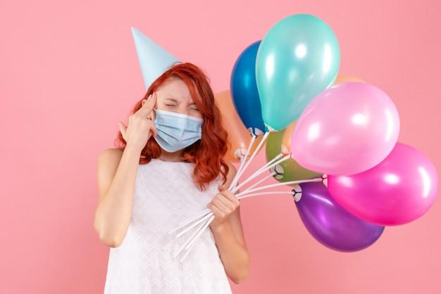 Jovem mulher segurando balões coloridos em máscara na rosa