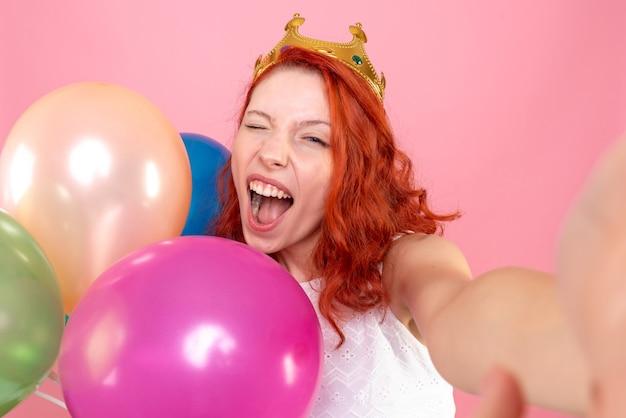 Jovem mulher segurando balões coloridos na frente de perto