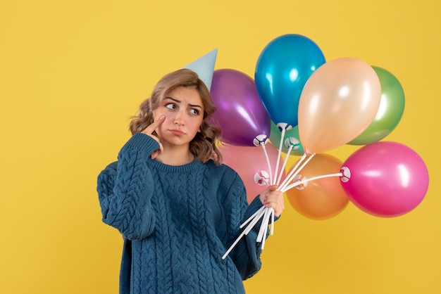 Jovem mulher segurando balões coloridos nas costas em amarelo