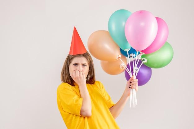 Jovem mulher segurando balões coloridos nervosos em branco