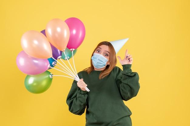 Jovem mulher segurando balões coloridos