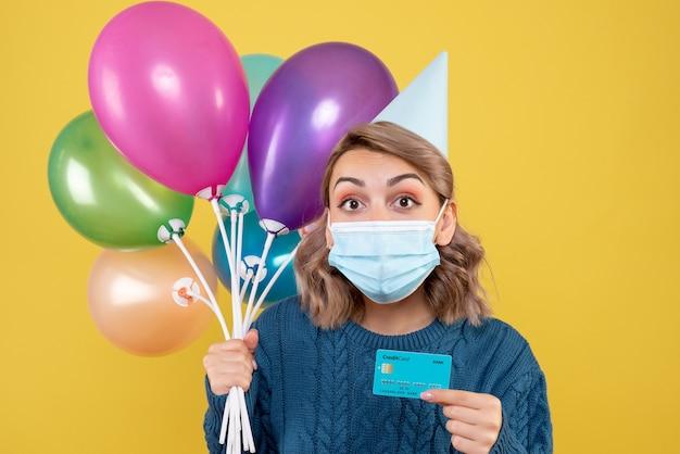 Jovem mulher segurando balões e cartão do banco em amarelo