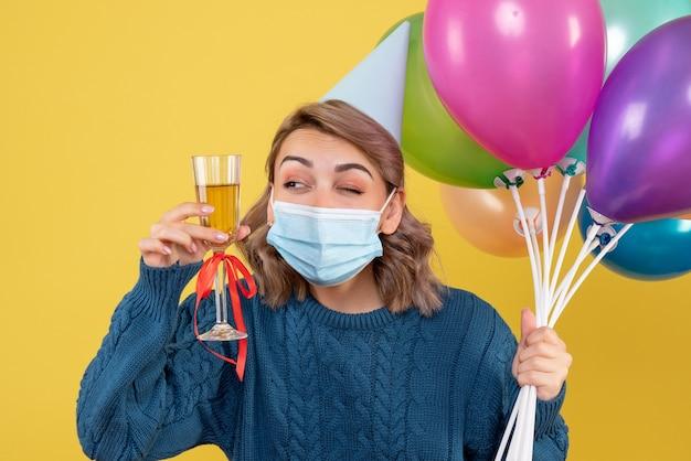 Jovem mulher segurando balões e taça de champanhe em amarelo