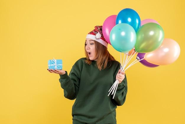 Jovem mulher segurando balões e um presentinho de frente