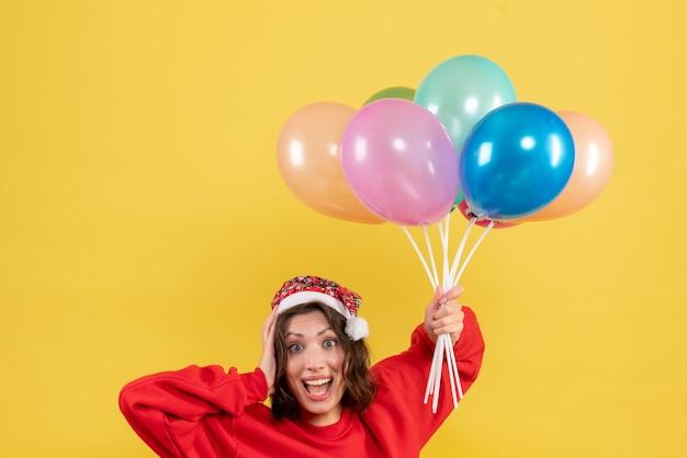 Jovem mulher segurando balões em amarelo de frente