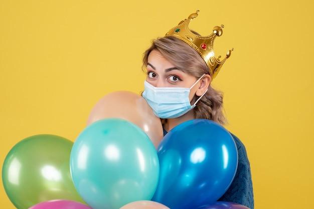 Jovem mulher segurando balões em máscara estéril em amarelo